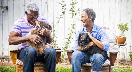 Couple in backyard with their dogs