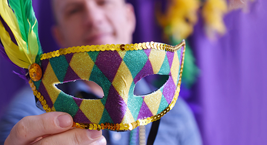 Man holding colorful Mardi Gras mask