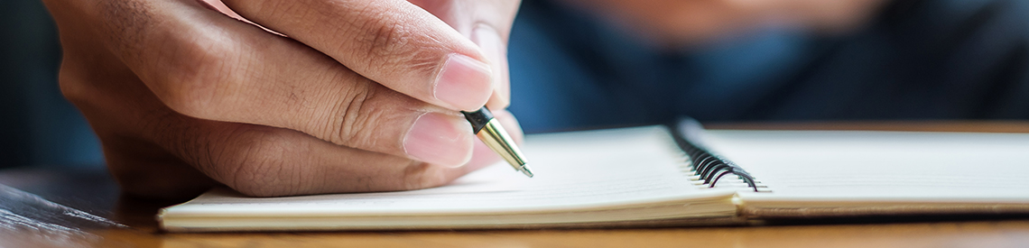 Close-up of hand writing in a notebook
