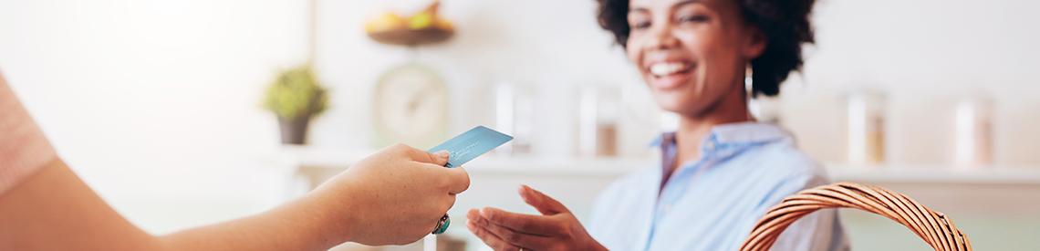 Woman using debit card in a store