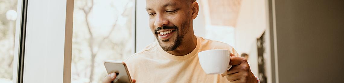 Man in coffee shop using smartphone