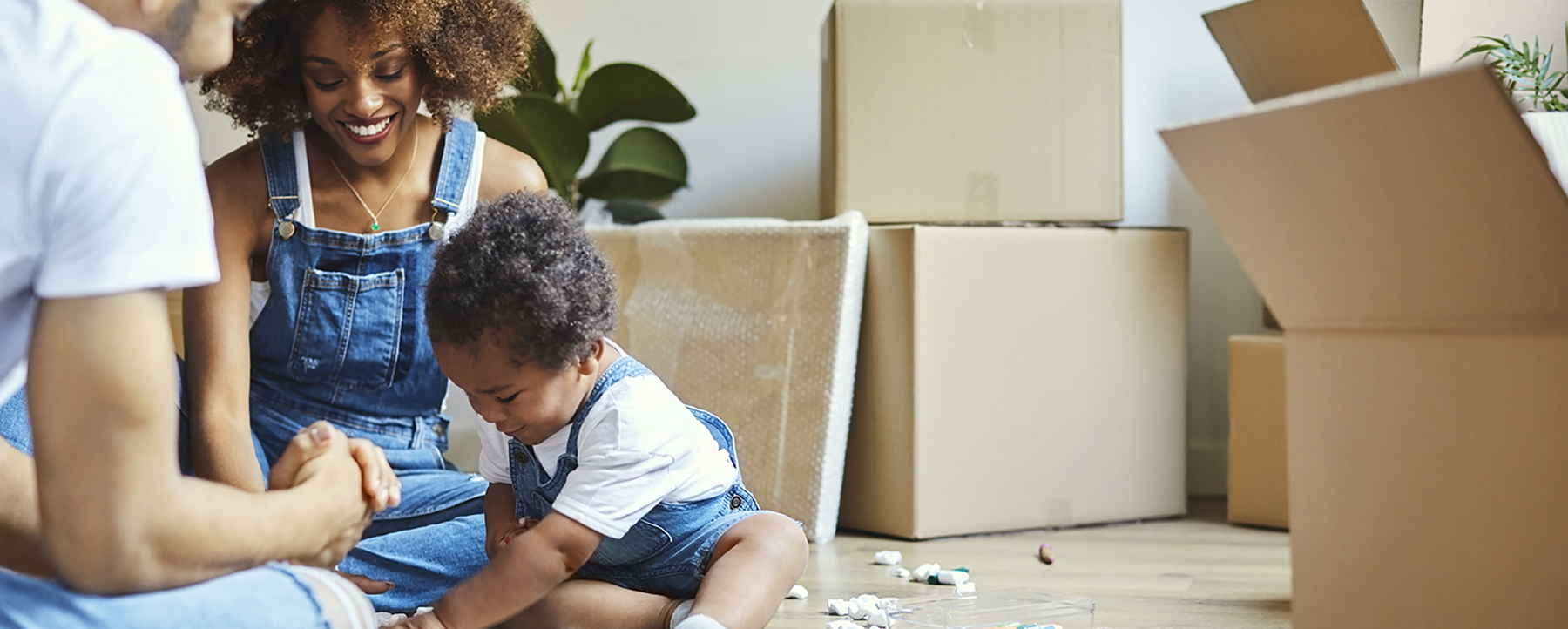 Father and mother with baby in living room unpacking boxes