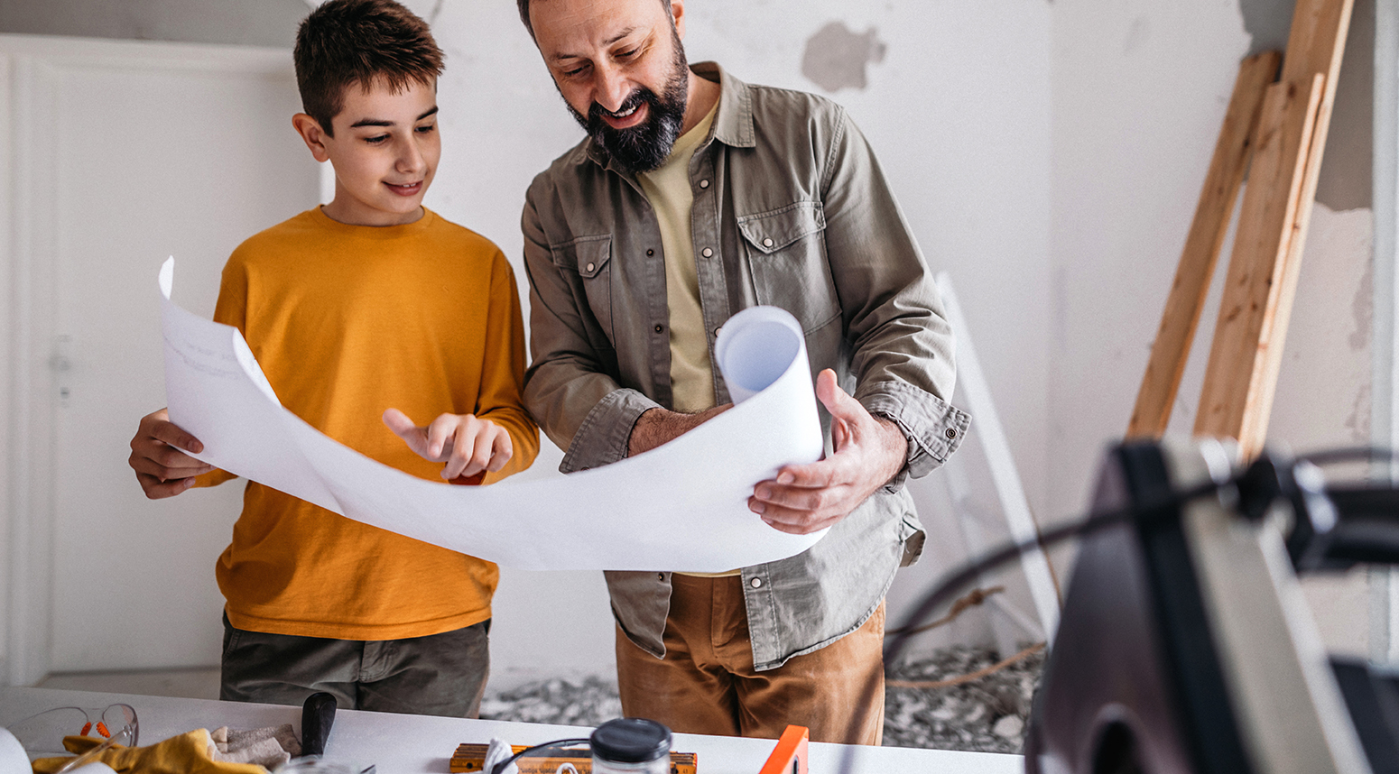 Father and son looking at blueprints in home